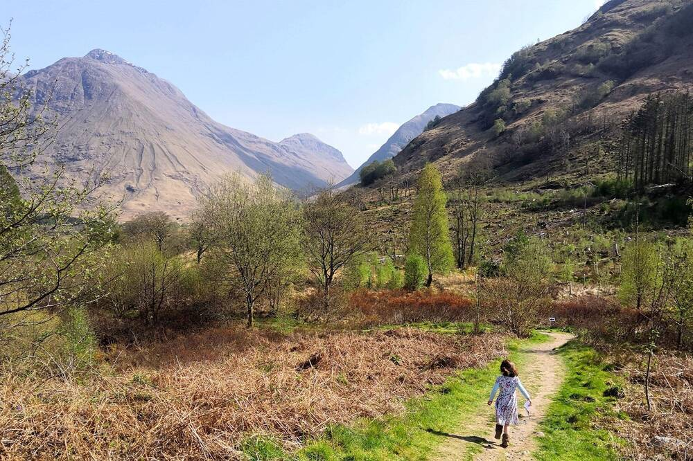 A little girl skips down a path into woodland, heading towards the glen.