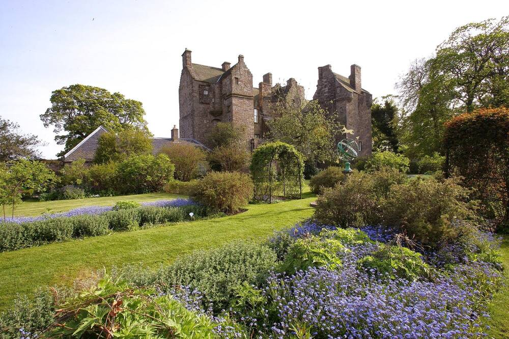 A view of Kellie Castle from the walled garden. The beds are planted with delicate purple flowers and herbaceous shrubs.