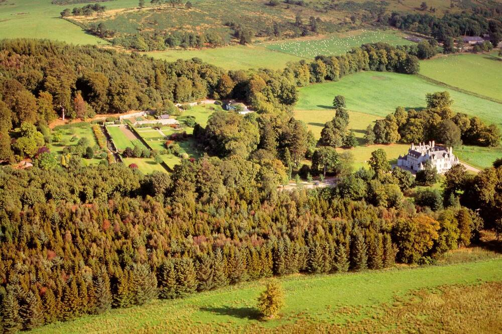 An aerial view of Leith Hall estate, showing the extensive woodland in autumn colour. The hall itself is nestled to the right of the image.