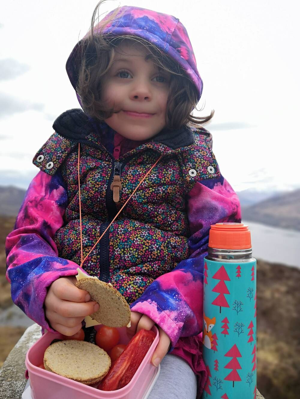 Small girl eating from a lunch box, with a loch behind her in the distance.