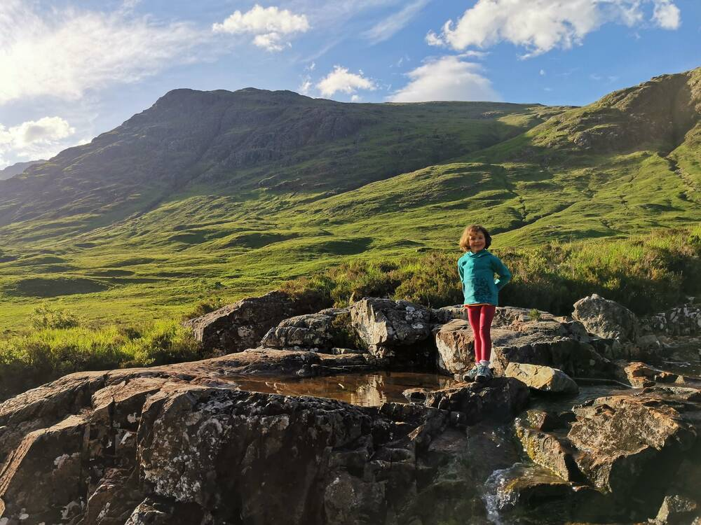Small girl stands by a rock in a mountain landscape
