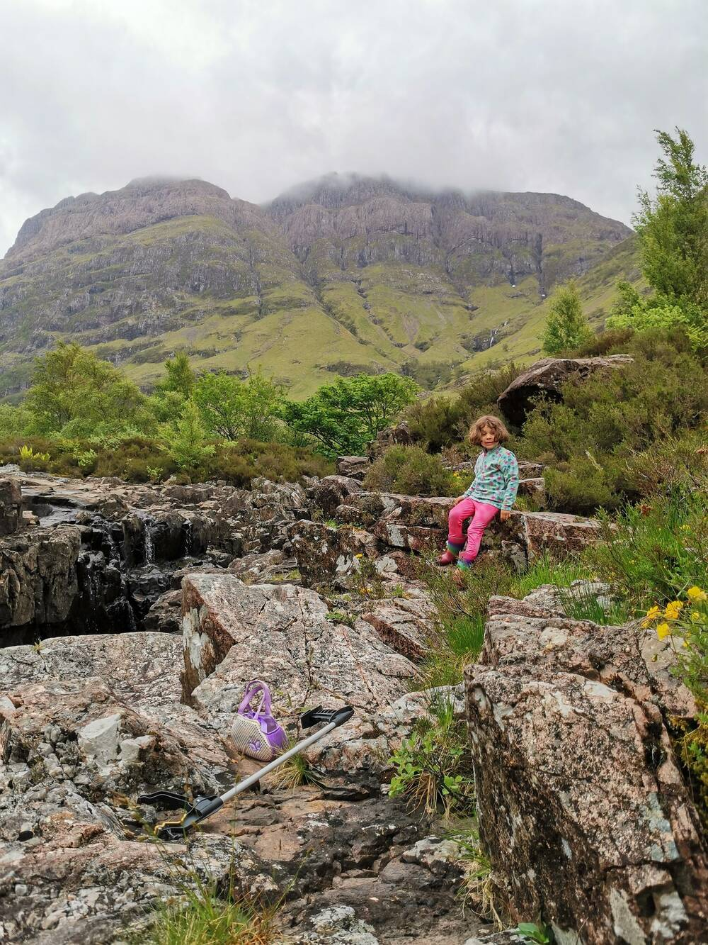 Small girl sitting on rocks in Glencoe