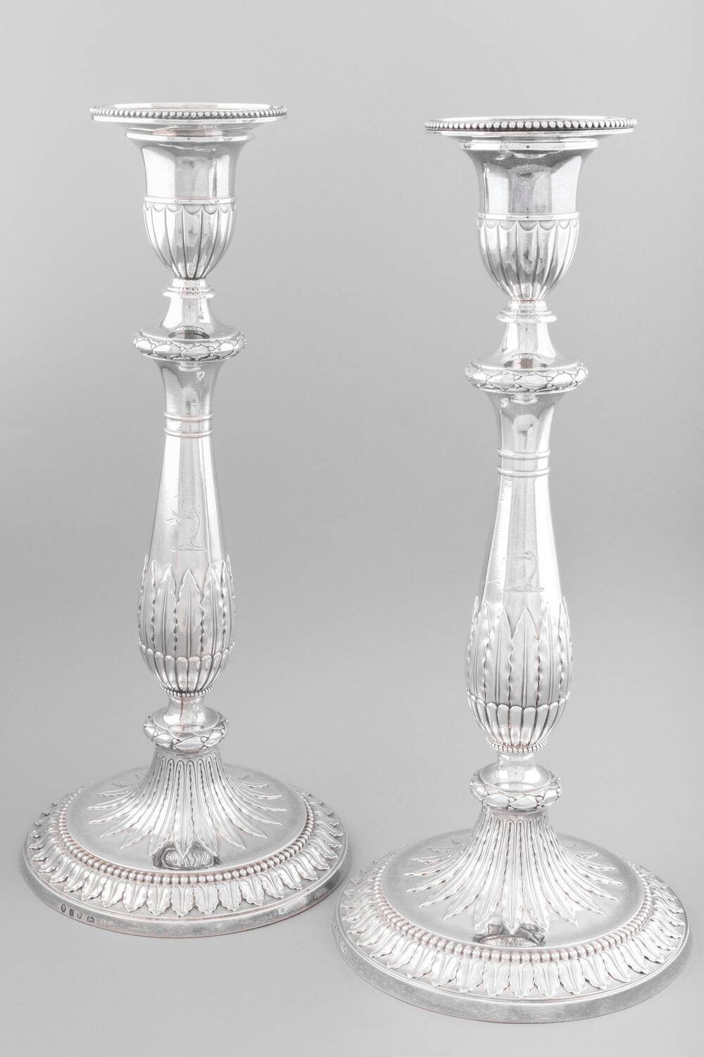 A pair of ornate silver candlesticks are displayed against a plain grey background. They have embossed decoration all around.