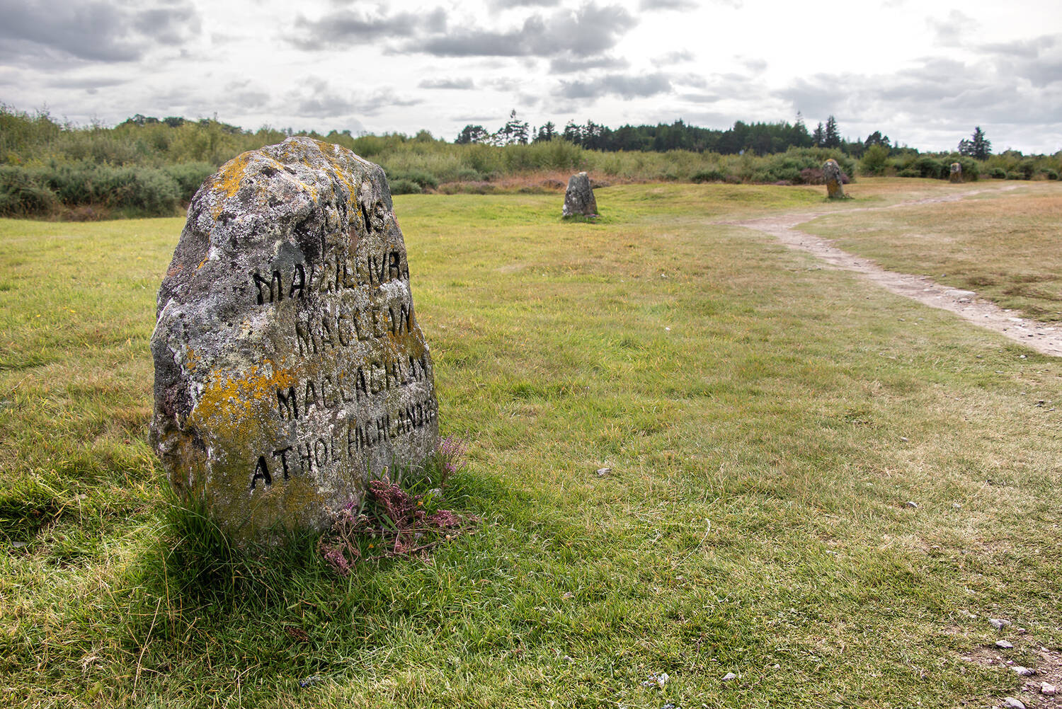 A stone marking the graves of several clans stands beside a narrow path on a field. Heather has been laid at the base. Several other grave markers can be seen in the background.