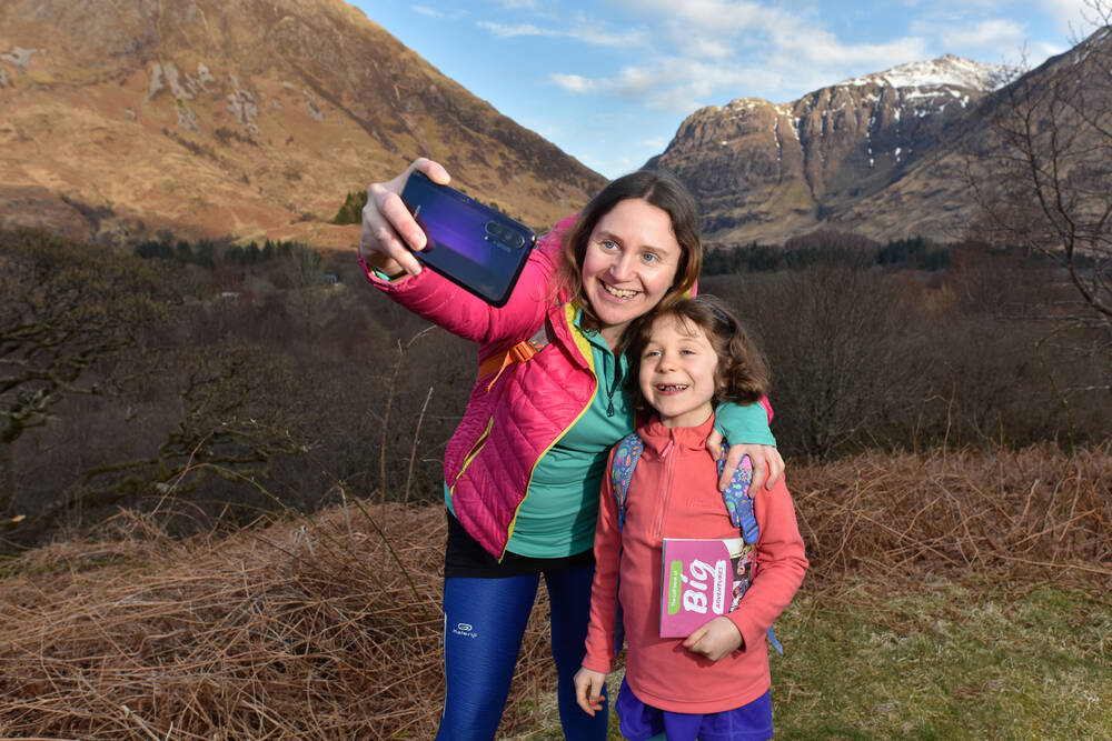 A woman and young girl pose for a selfie with mountains behind