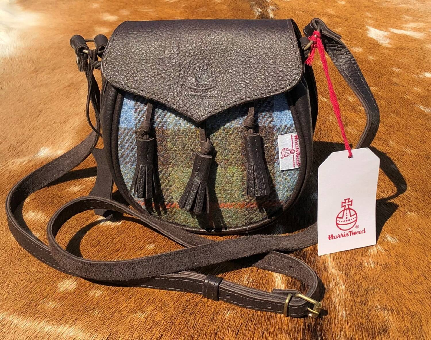 A leather handbag shaped like a sporran, with a tweed middle panel. It has a long thin shoulder strap. It has a label declaring it is made from official Harris tweed.