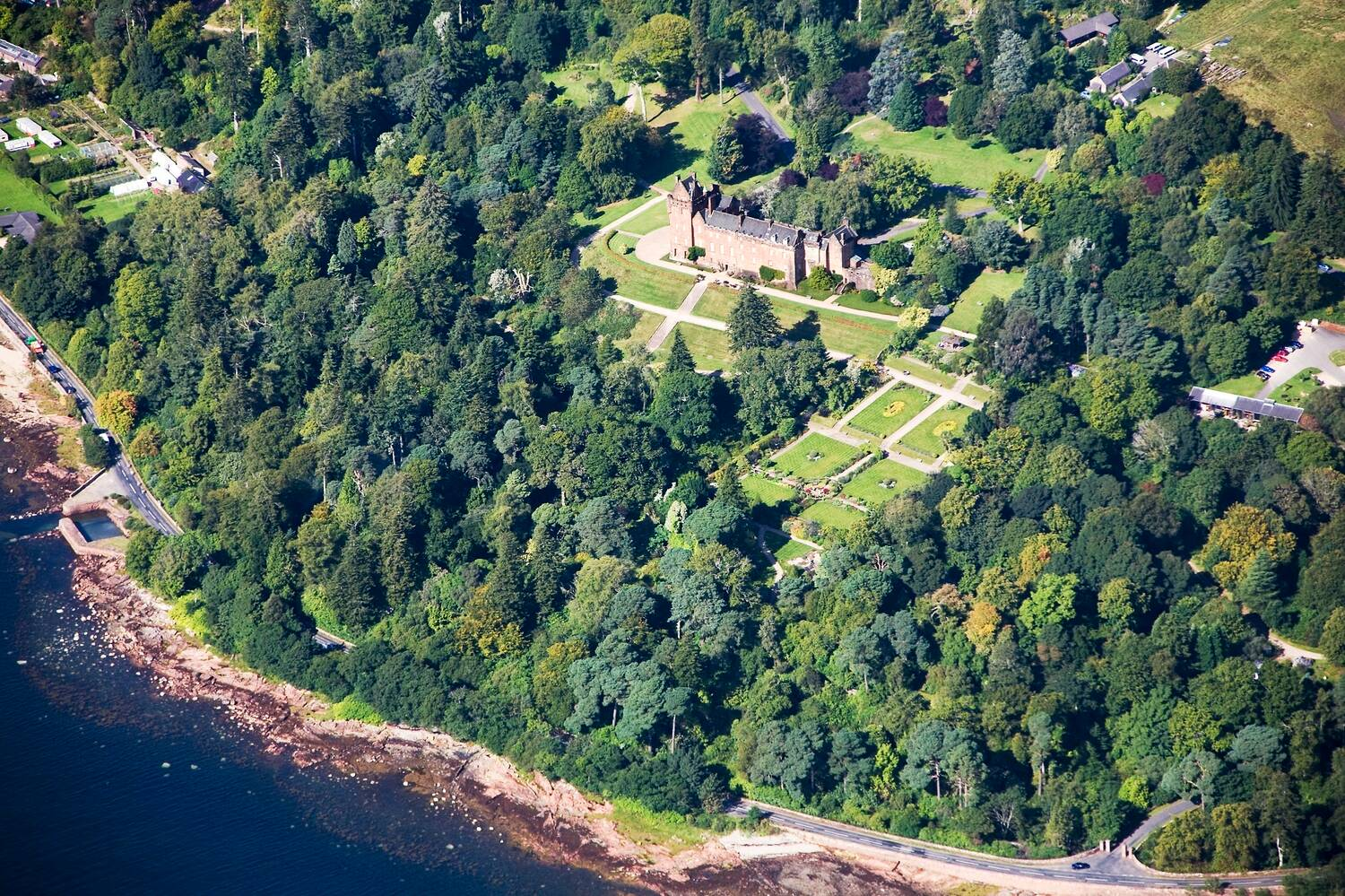 An aerial view of Brodick Castle, Garden and Country Park on Arran. The glistening blue bay can be seen in the bottom left corner. The castle can be seen with the garden in front, all surrounded by green woodland.