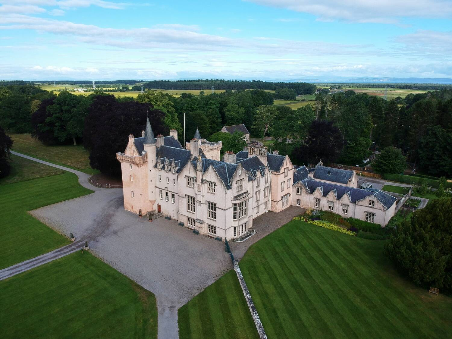 An aerial view of Brodie Castle, showing the building surrounded by manicured lawns and woodland. A large gravel drive with several paths leading off lies in front of the castle.
