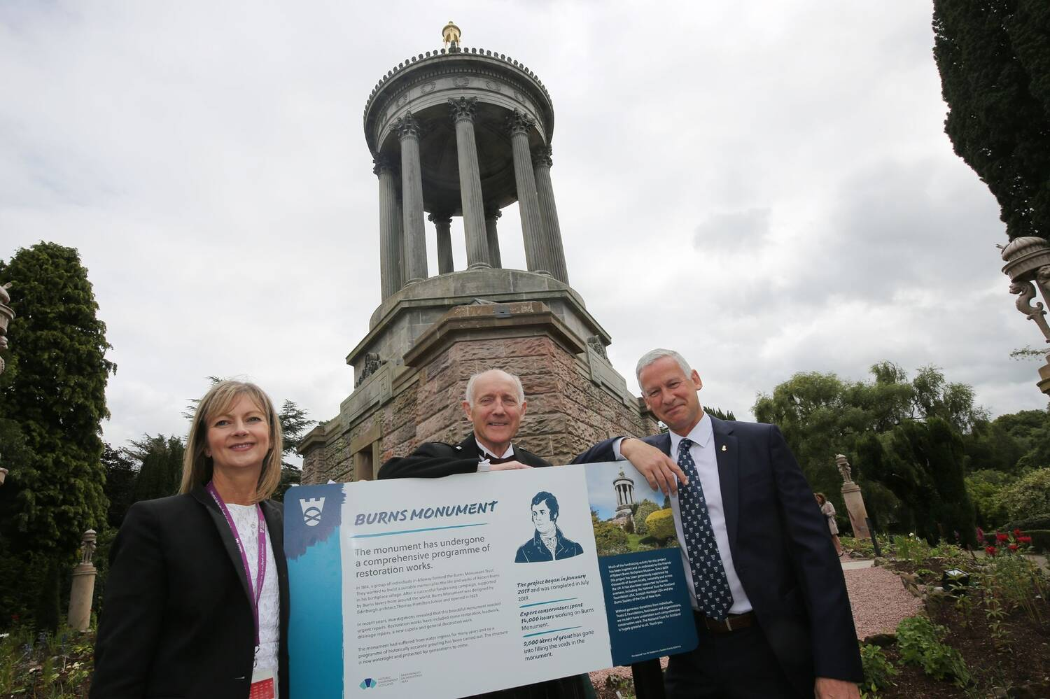 Three people stand beside an interpretation board in front of Burns Monument.