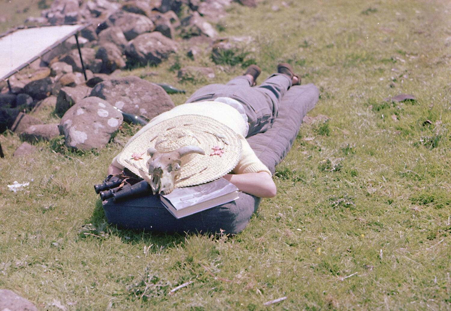 A lady lies on her tummy on the grass, with a straw hat covering her head. A book and some binoculars lie by her head. A sheep's skull has been balanced on the hat.