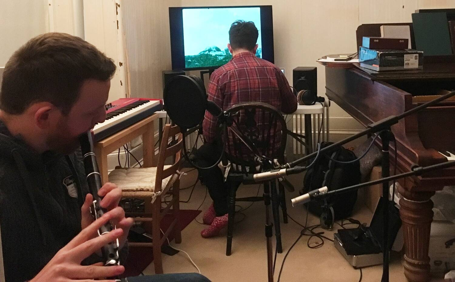 Two men sit in a recording studio in Canna House. One plays a flute while the other sits at a computer, editing video content.