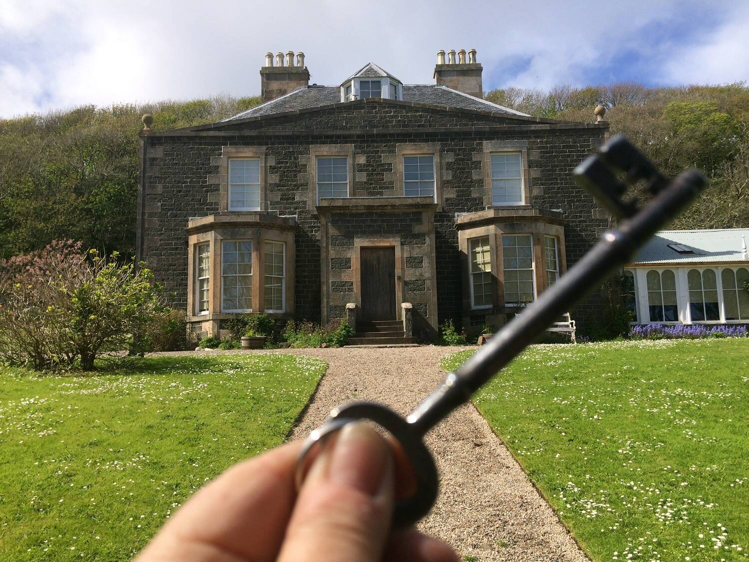 A hand holds up a mortice key in front of Canna House. A gravel path crosses a lawn and reaches a large wooden front door.