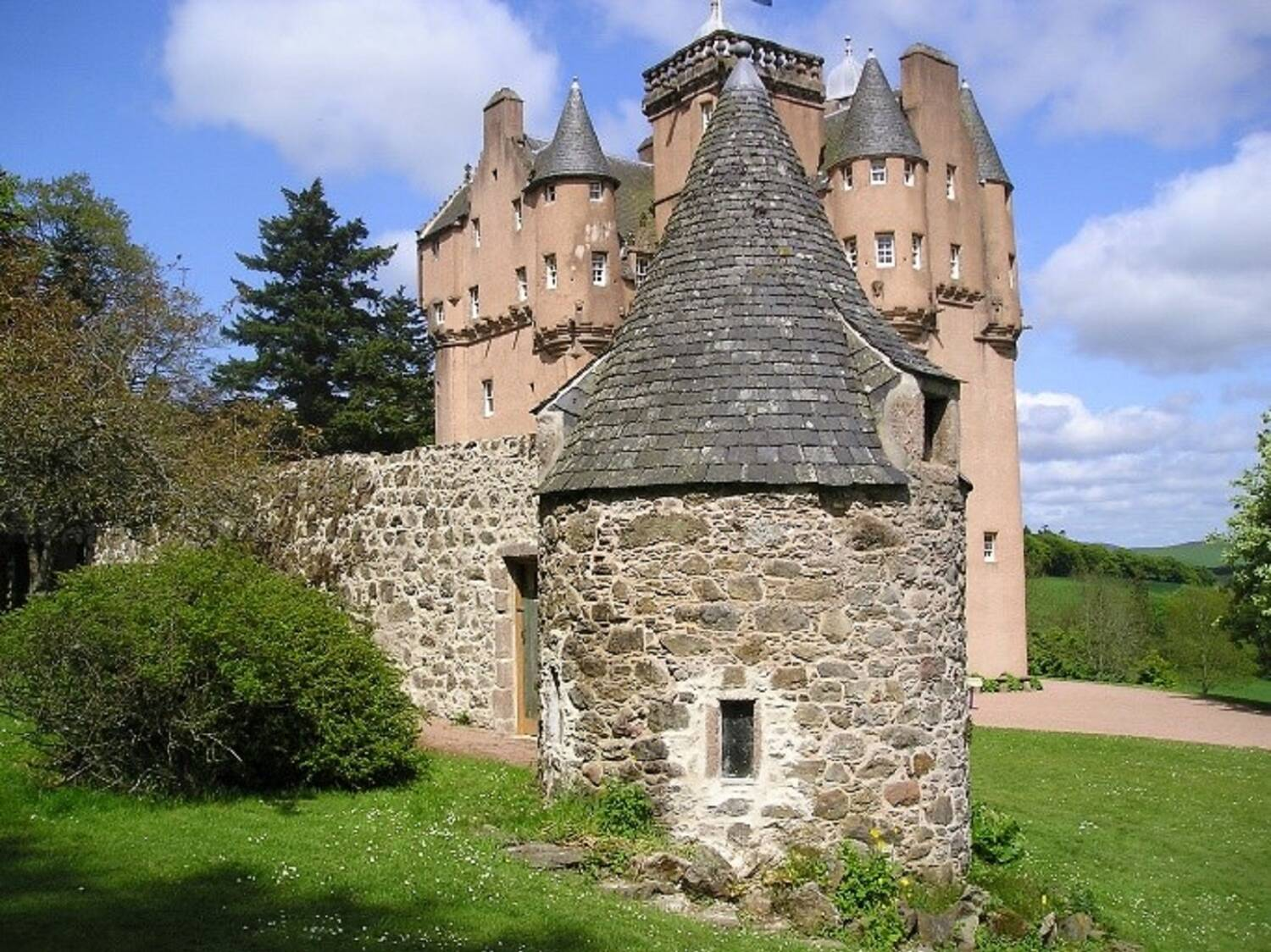 A view of a tall, turreted, pink-walled castle, with an older stone wall in the foreground. At the corner of the wall is a small tower, with a slate tiled conical roof. Green lawns, tall trees and shrubs otherwise surround the castle.