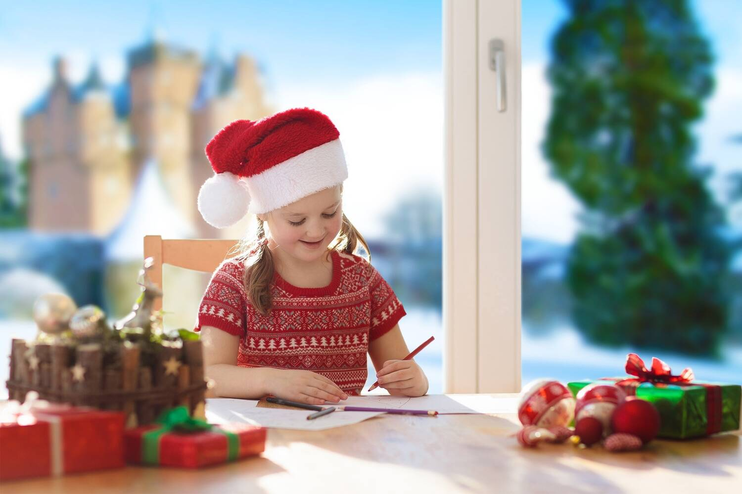 A young girl, wearing a Santa hat, sits at a white table, writing. Craigievar Castle and a shaped yew tree can be seen through the window in the background.