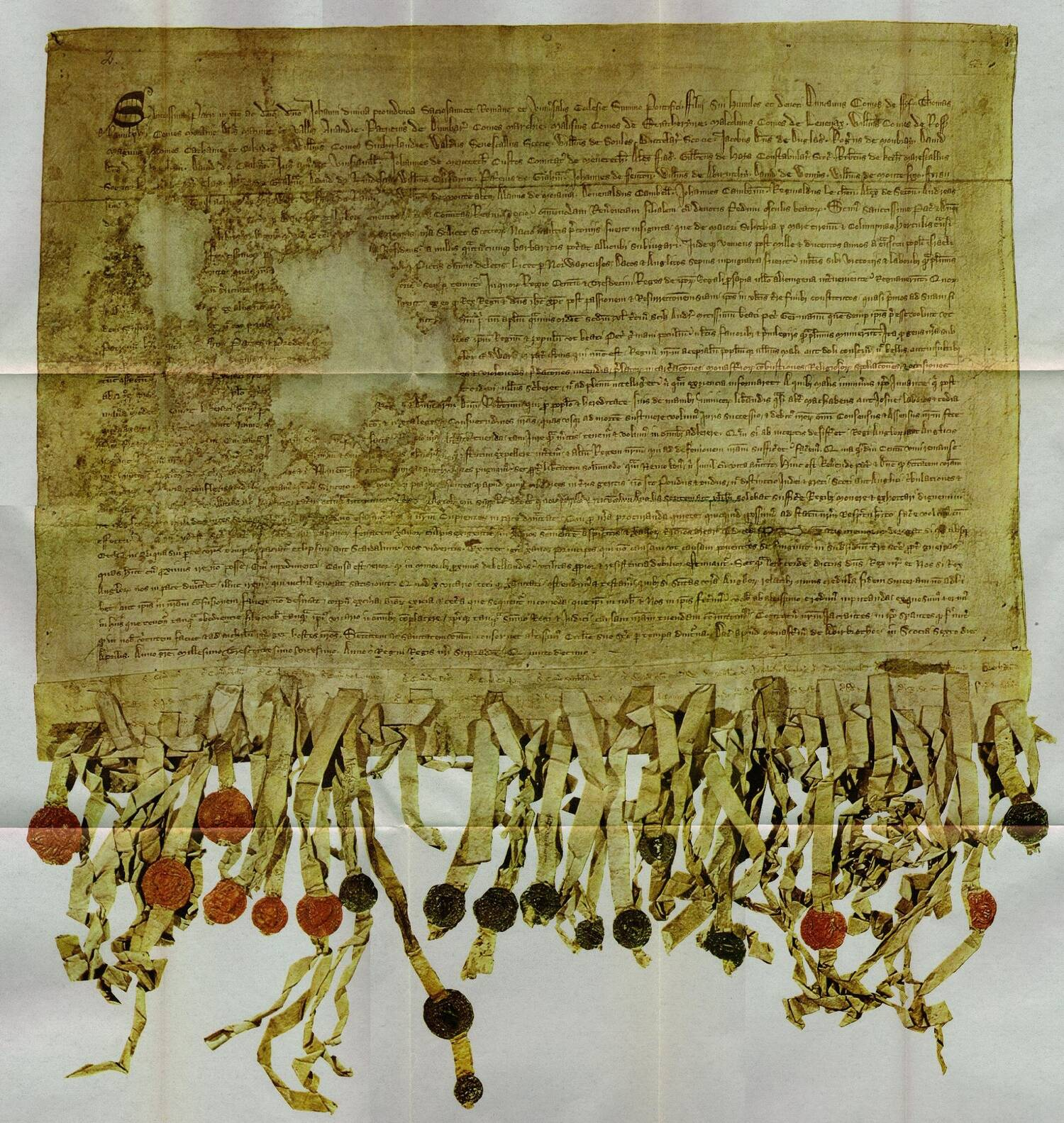 The manuscript of the Declaration of Arbroath on yellowed paper. Strips of paper with wax seals are attached to the bottom.