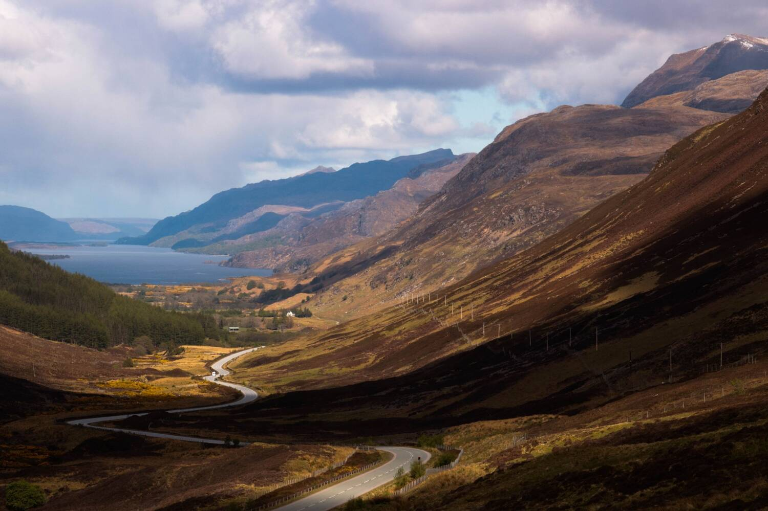 A view from a mountain pass looking down a winding road towards a loch.
