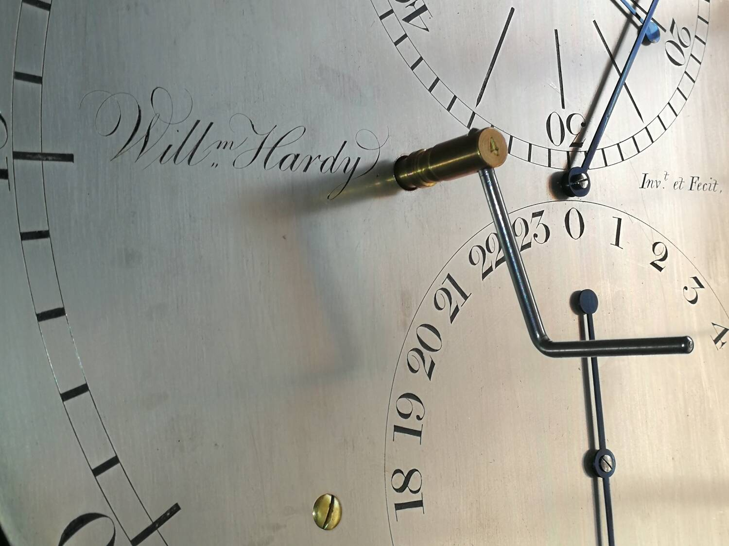 A close-up of a silver dial on a clock face. It features two circles, one numbered for minutes and the other for hours. It is engraved with the maker's name: Willm Hardy.