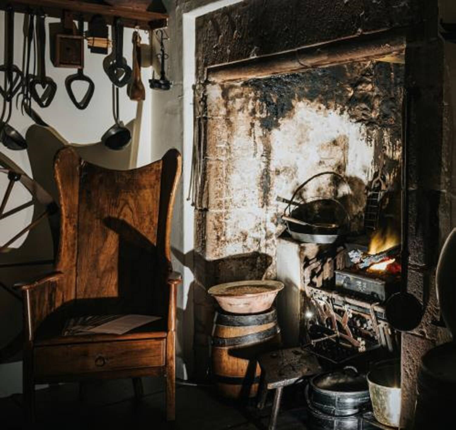 A photograph of a dark corner of an old kitchen. A wooden armchair sits beside a stone fireplace with various pots and pans beside it. Utensils hang on the wall behind the chair.