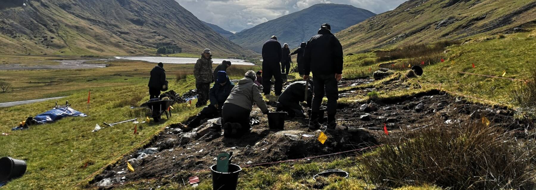 A group of volunteers stand by an excavation site in Glencoe.
