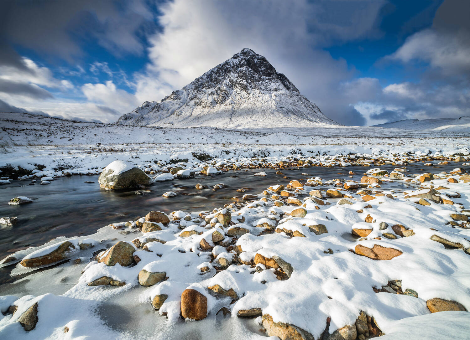 A pyramid-shaped mountain rises dramatically from a rocky moorland landscape. It is covered in snow, with dark rock exposed at the top. Clouds scud across a bright blue sky.