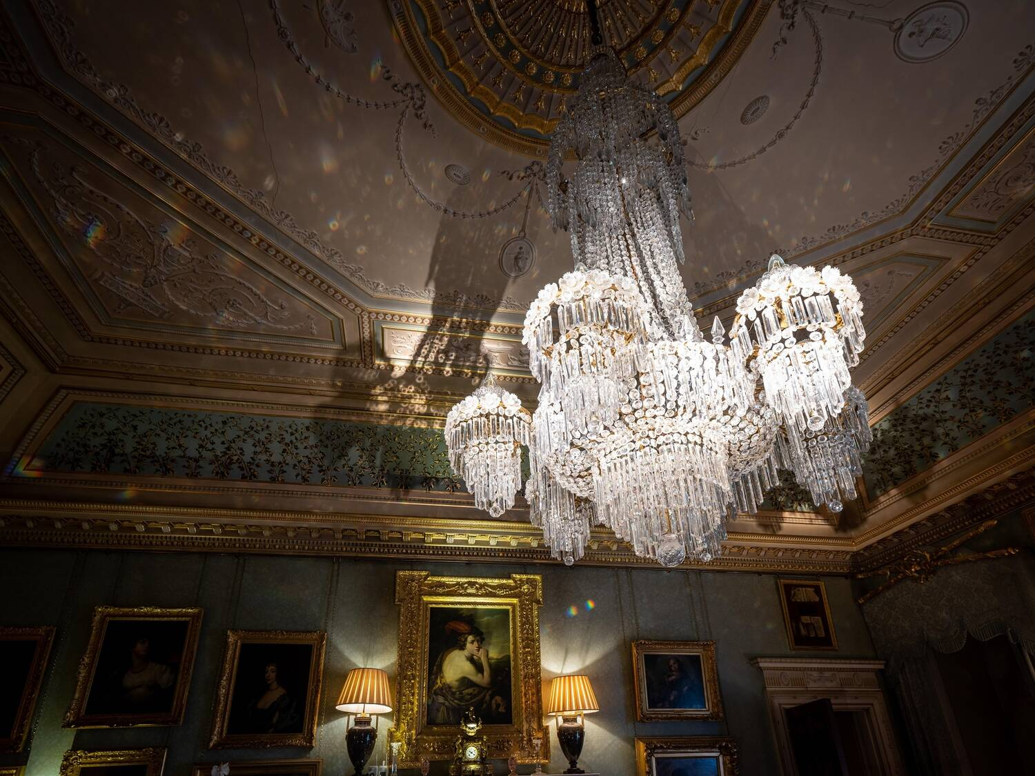 A very large crystal chandlier hangs from an ornate ceiling. It is lit. Its shadow falls onto the decorated wall panels behind, below which are displayed a number of gilt-framed portraits.