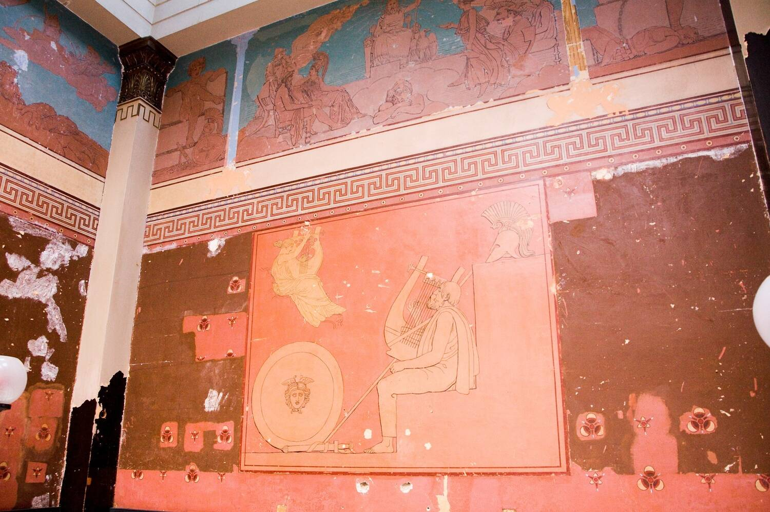 A wall in the dining room at Holmwood with a classical mural and designs stencilled on.