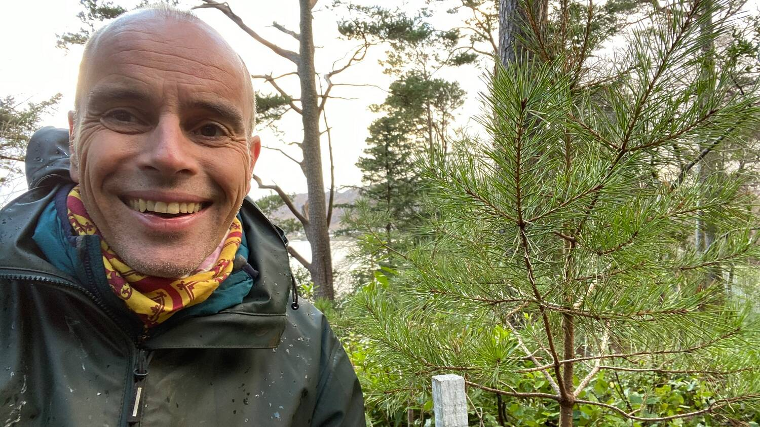 A close-up photo of a man, wearing waterproof clothing, standing in woodland beside a small pine tree. He is smiling.