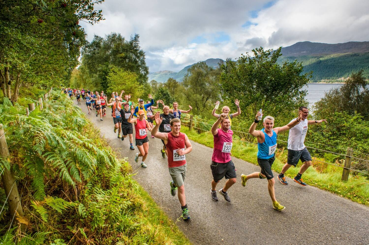 A group of marathon runners run on a tarmac path beside Loch Ness. Many look towards the camera and raise their hands in the air.