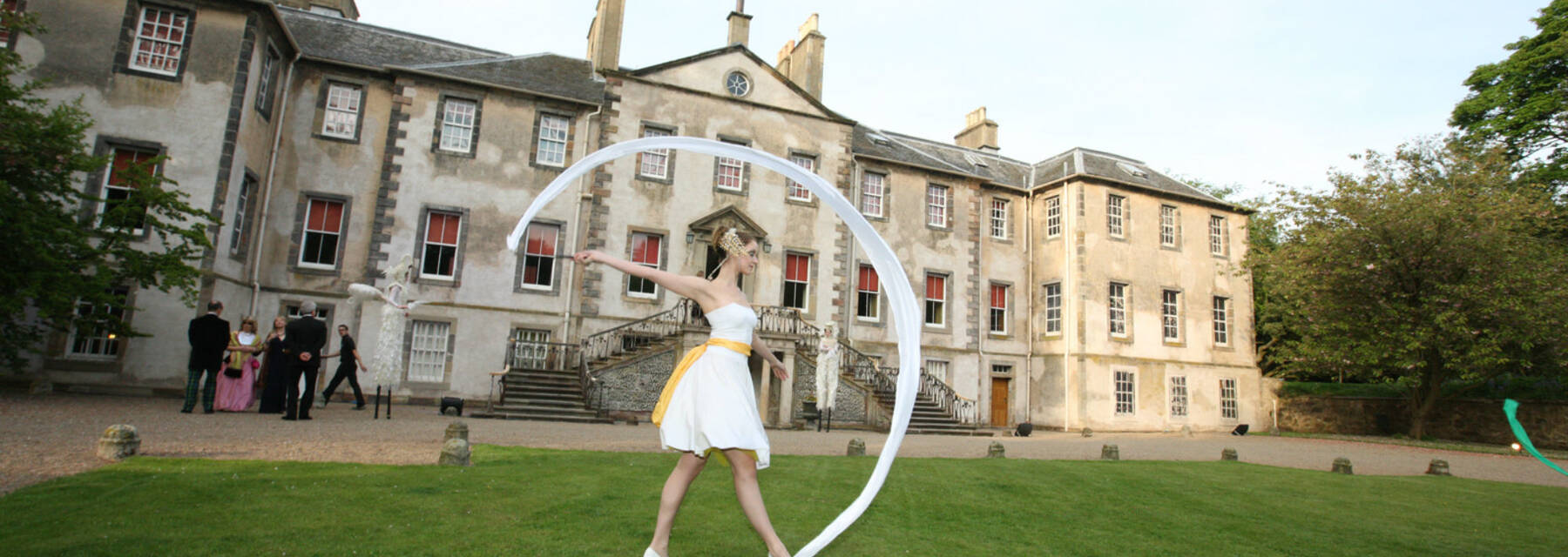 A girl stands with a gymnastic ribbon on the lawn in front of Newhailes House
