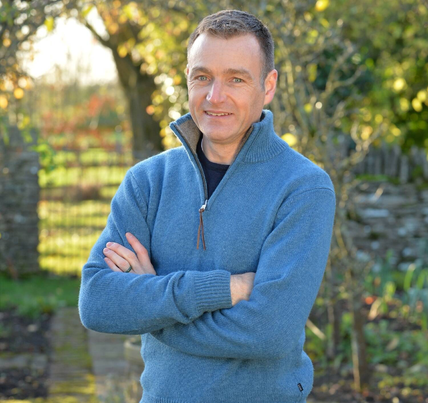 Chris Beardshaw stands in a garden, smiling at the camera with his arms folded in front of him. He wears a bright blue woolly jumper, with a half zip.