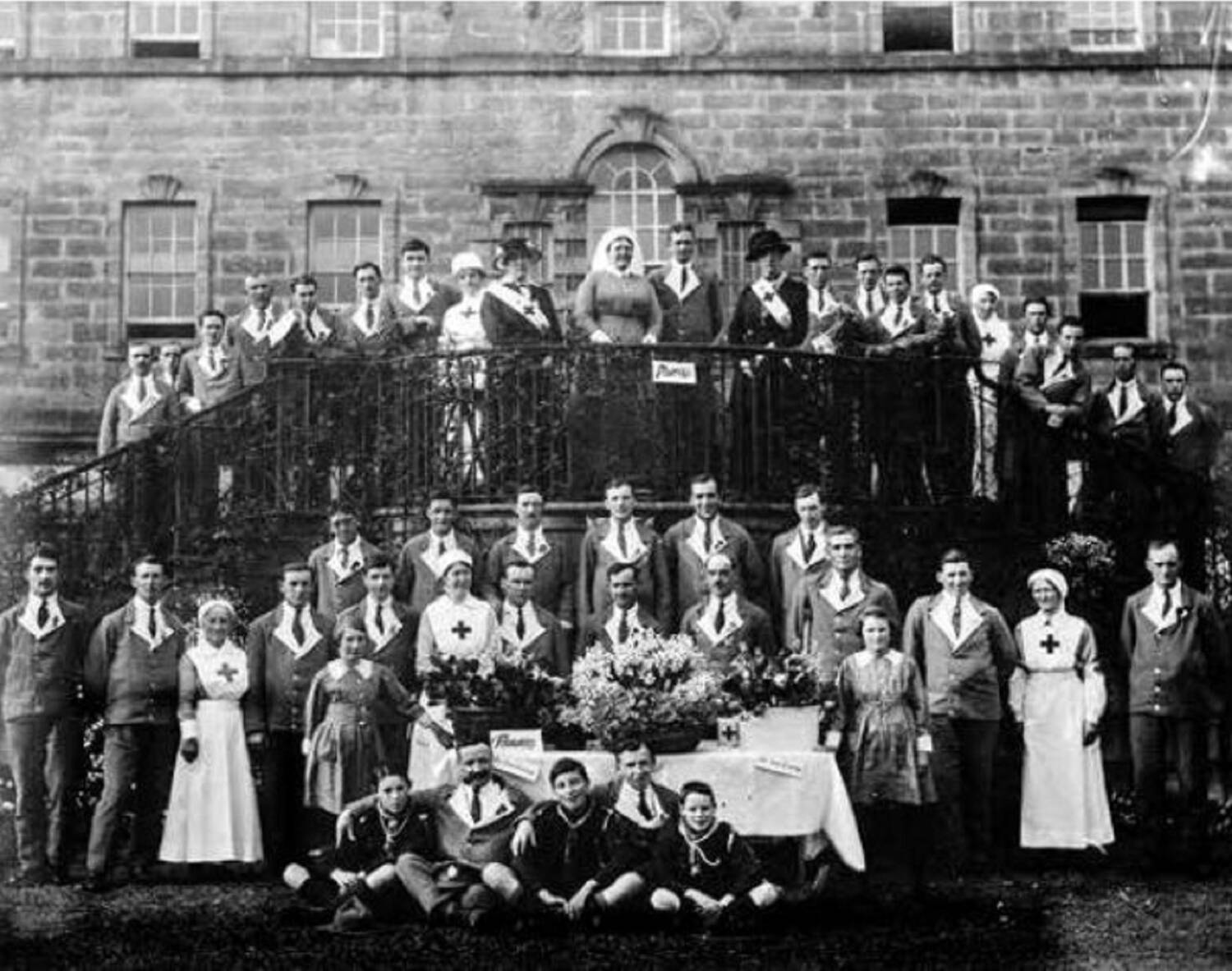 A black and white photograph of around 50 people standing on or around steps in front of a grand country house. It appears to be a fete or celebration of some kind as all are smartly dressed. Nurses are in uniform and men wear jackets and ties.
