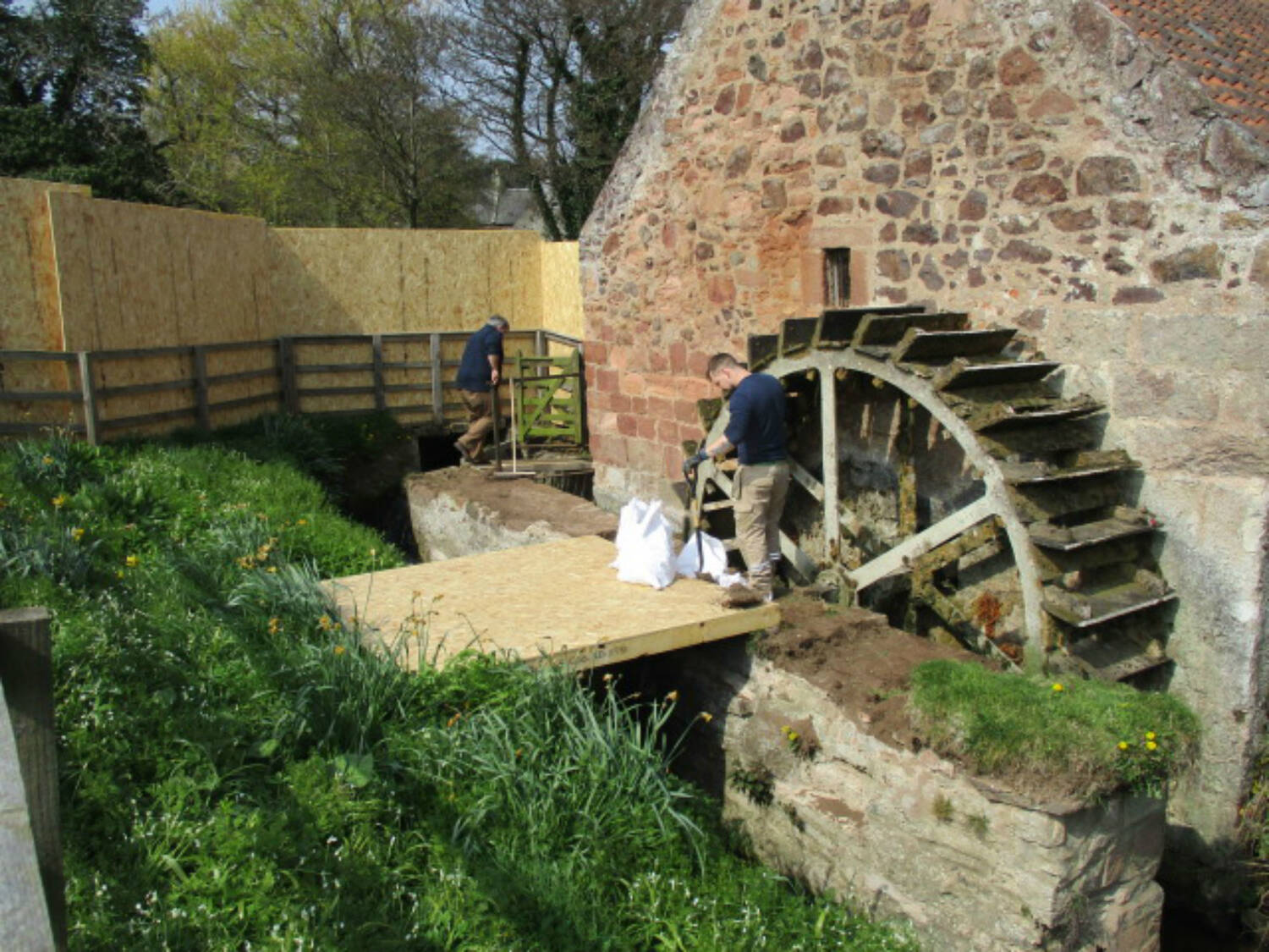 Two men work on the water wheel, surrounded by wooden boards.
