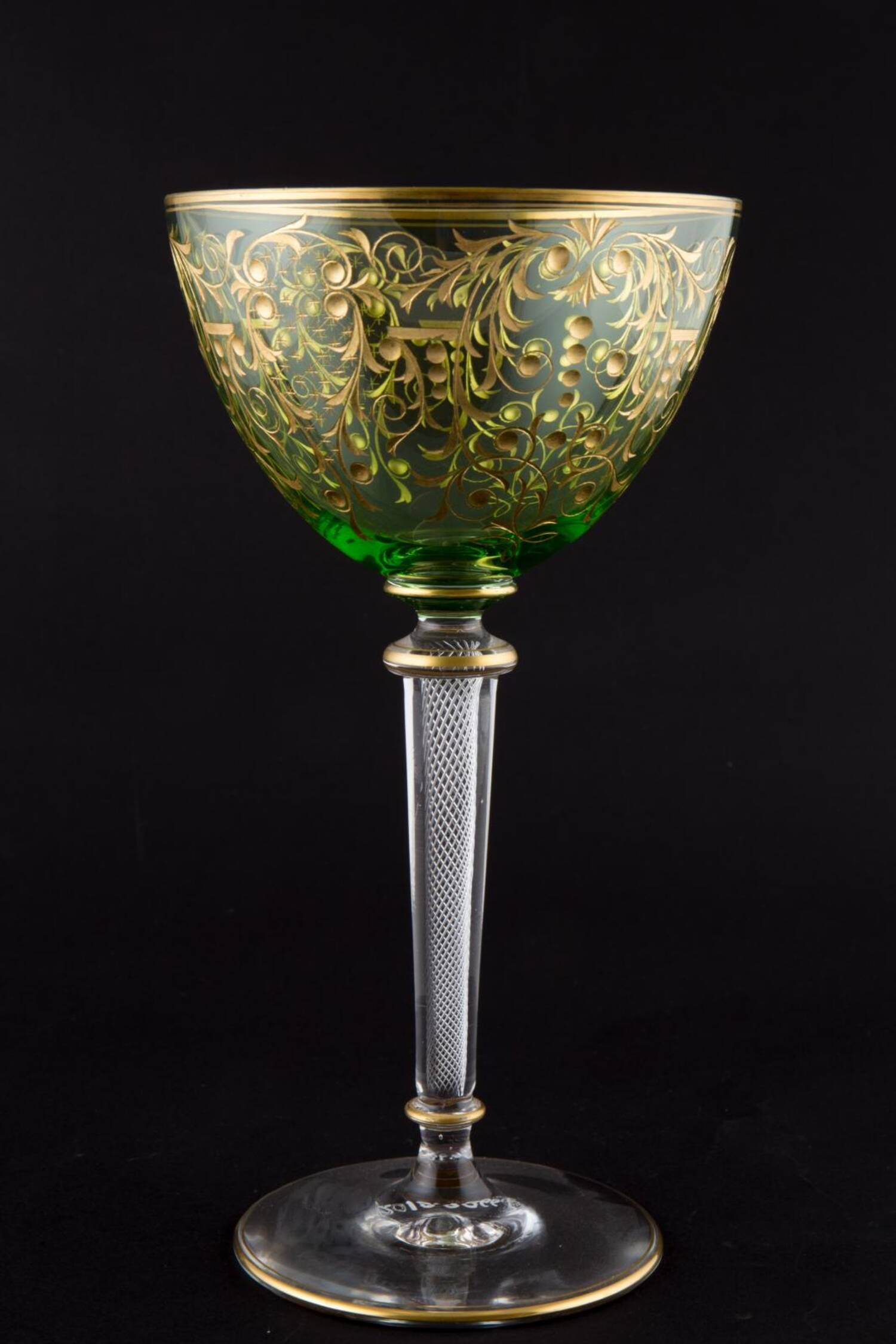 A French champagne glass used at Fyvie Castle. The glass is partially gilded with an elaborate pattern, and has a green colour. The stem has a delicate lattice-type silver decoration.