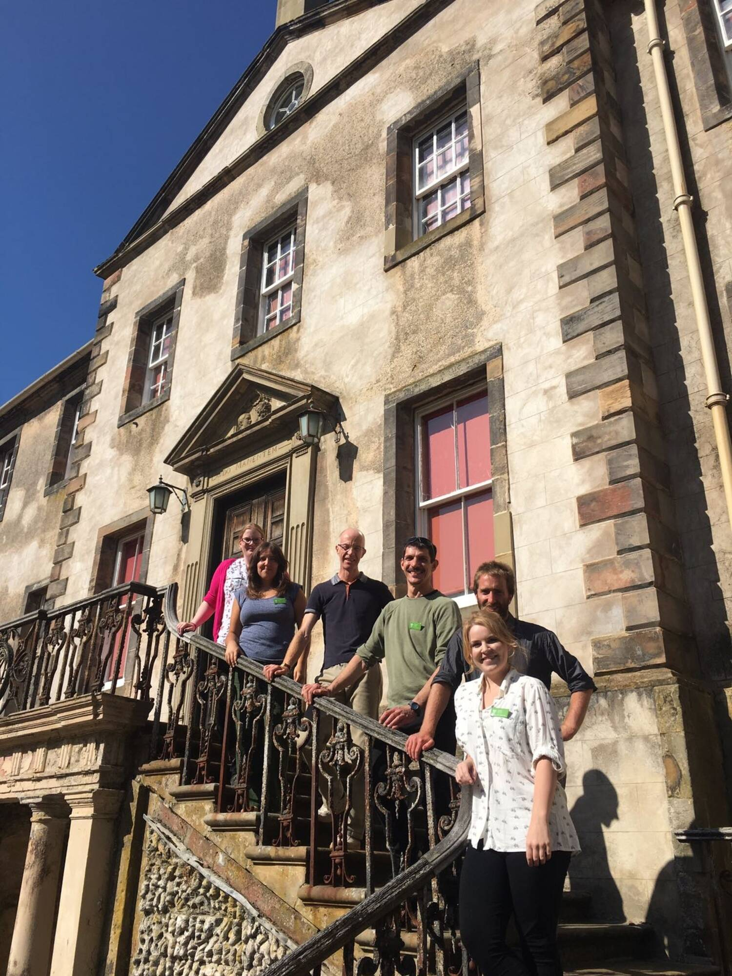 6 people stand on ascending exterior steps of Newhailes House, holding the handrail, on a bright sunny day.