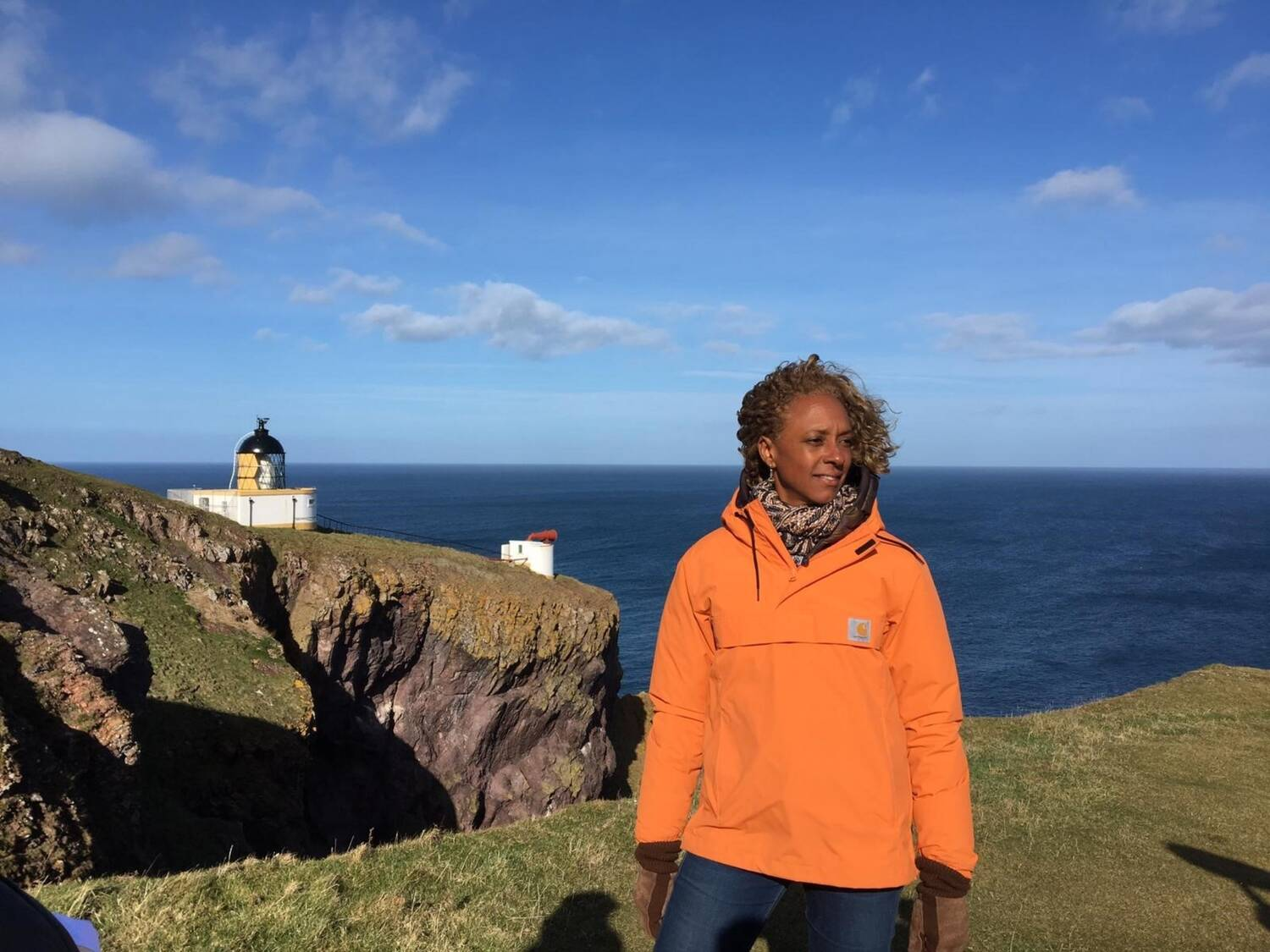 Gillian stands on the cliffs at St Abb's Head wearing a bright orange jacket. The lighthouse is in the background. The sky and sea are deep blue.