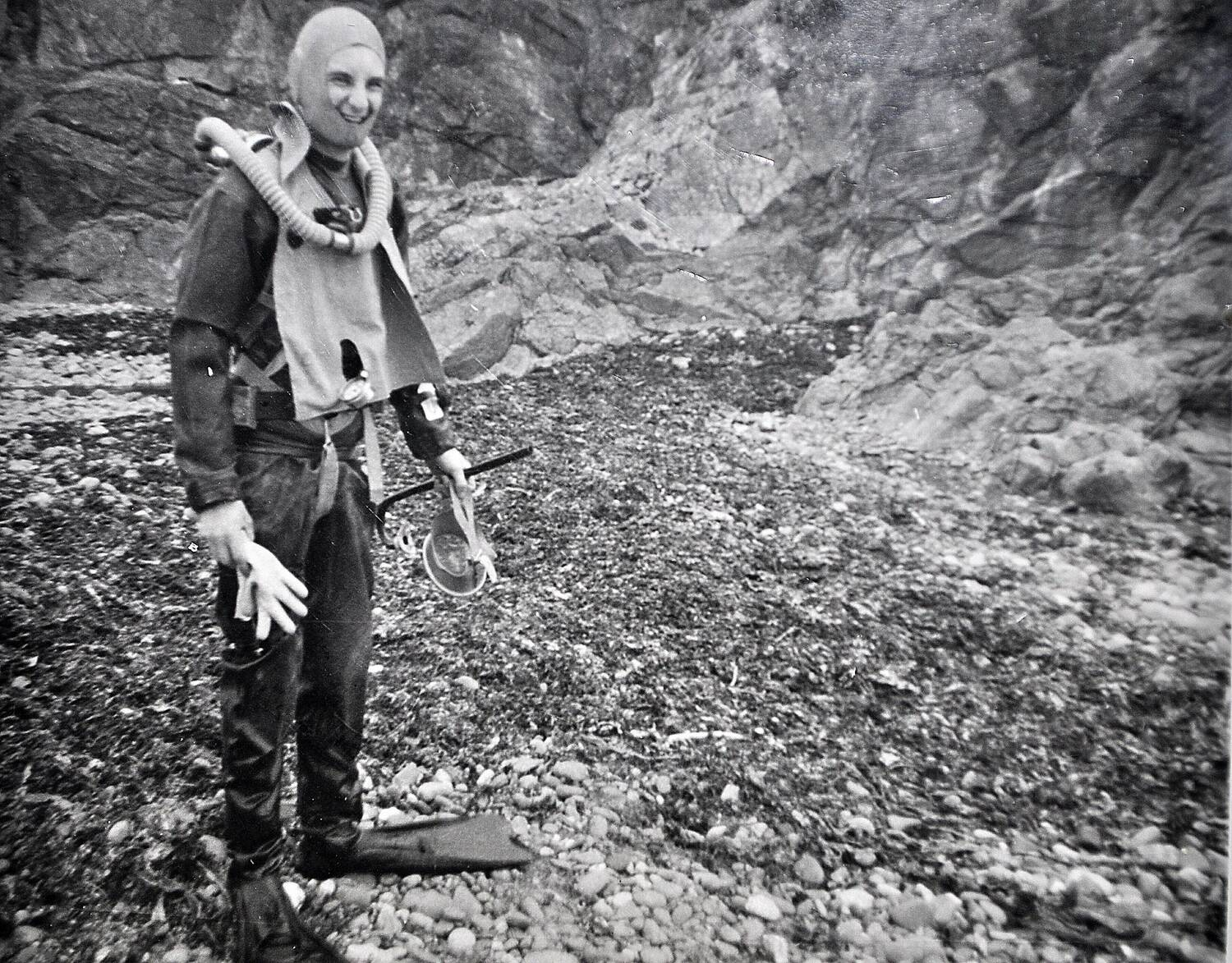 A black and white photo of a man in a diving suit with flippers, standing on a pebbly beach. A steep rock face can be seen in the background.