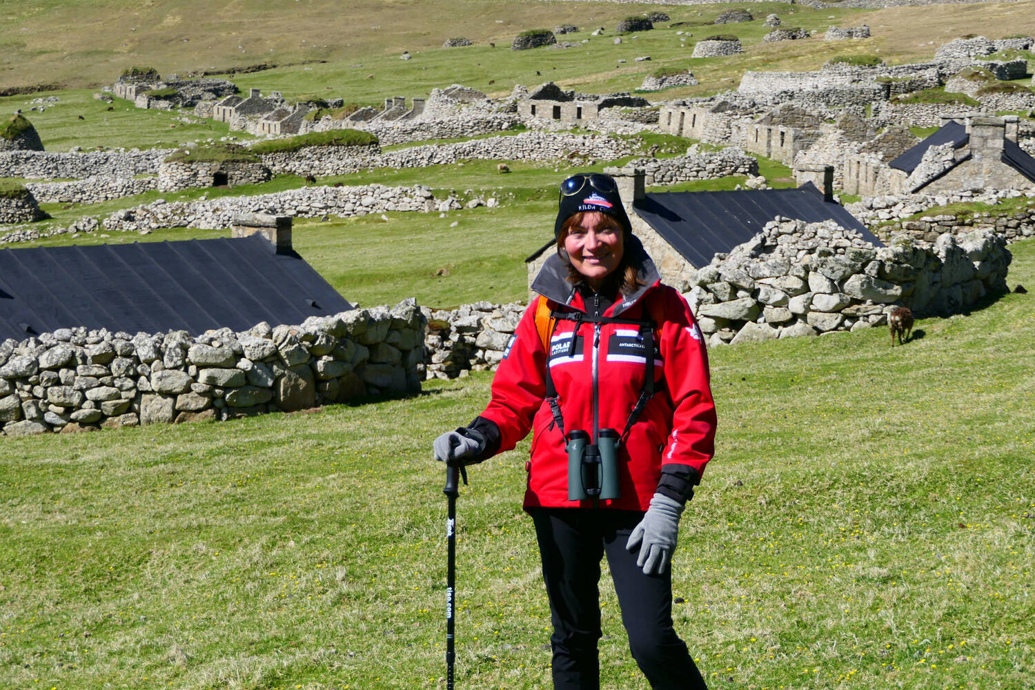 Lorraine Kelly stands with a walking pole in a field in Village Bay. Stone houses and sheep are in the background.