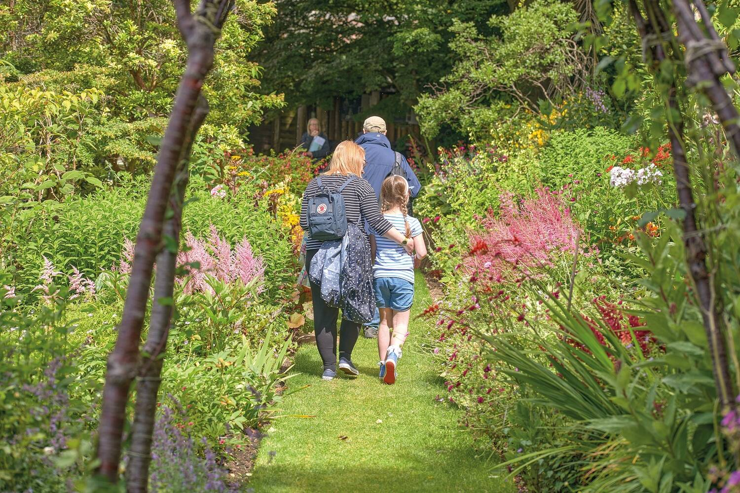A mum walks away from the camera, with her arm around her young daughter's back, along a grass path in a pretty garden. A man walks just ahead of them.