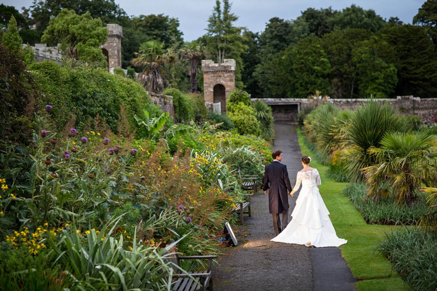 A bride and groom walk hand in hand along a path in a beautiful, colourful walled garden. Tall trees stand in the background, behind the walls.