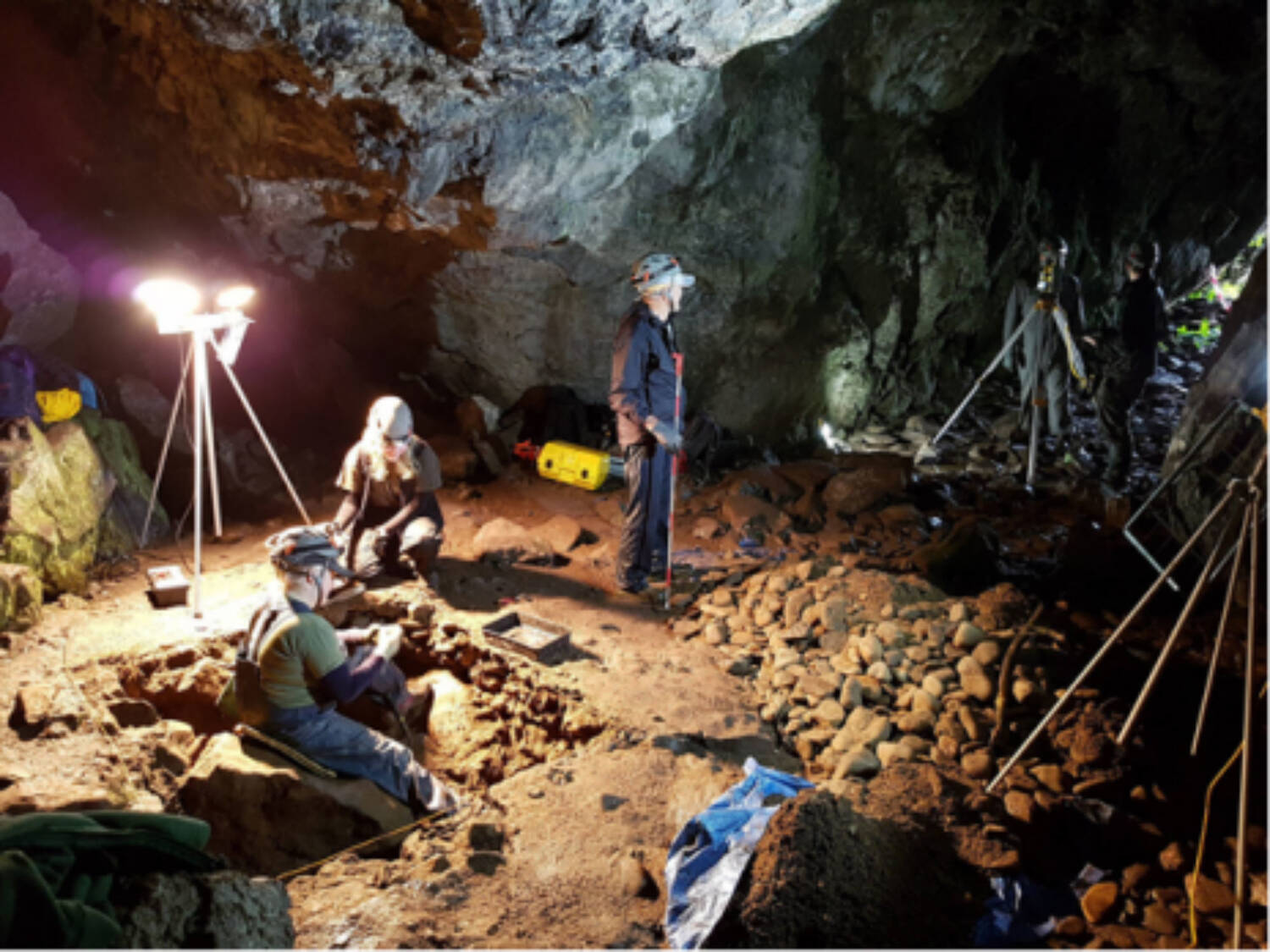A group of people work in a cave, lit with lamps. A hole has been dug in the floor, and one person sits on a large rock in the hole.