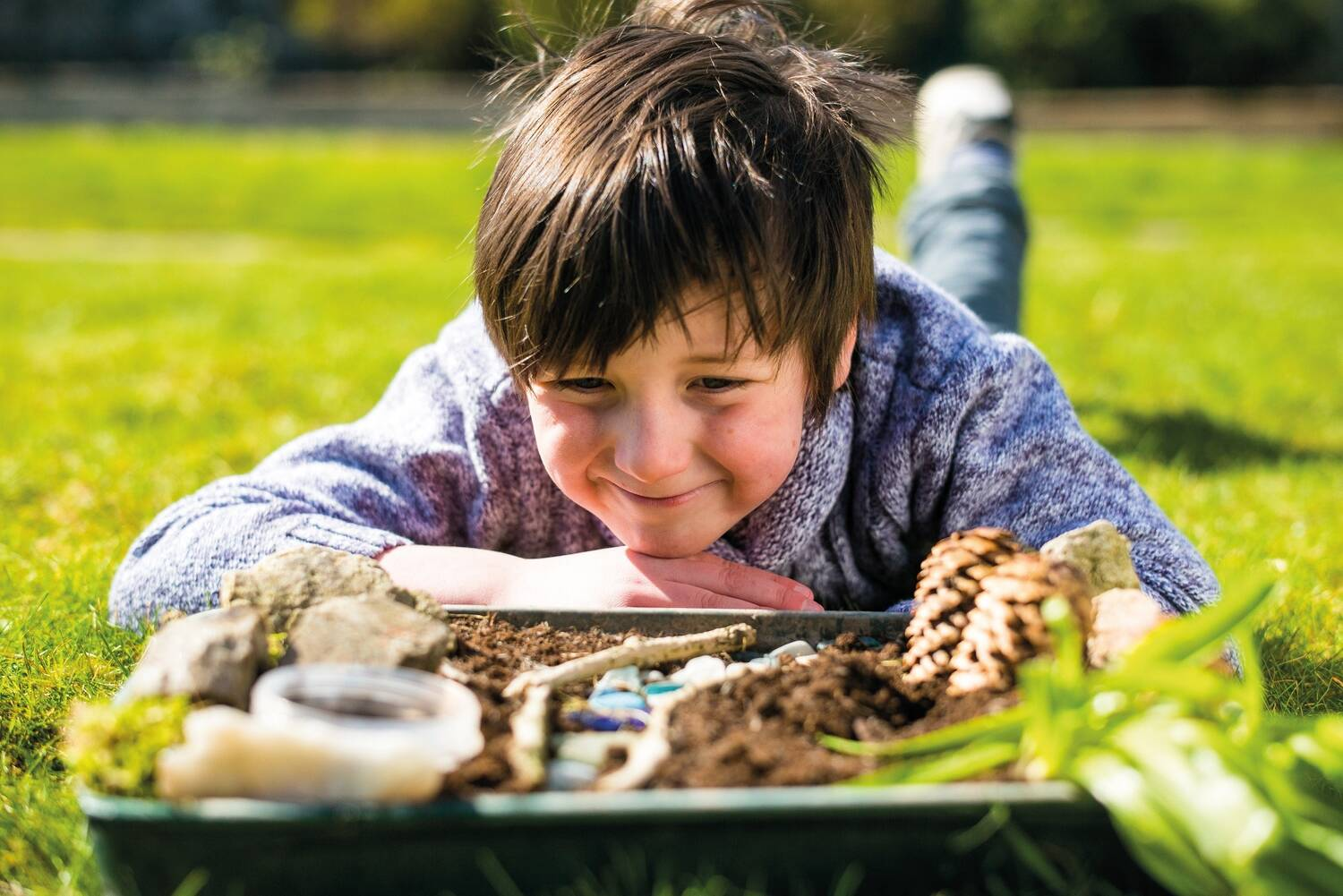 A boy lies on the grass on his tummy, resting his chin on his hands. In front of him is a planting tray, filled with soil, pine cones, stones and twigs. He is smiling.