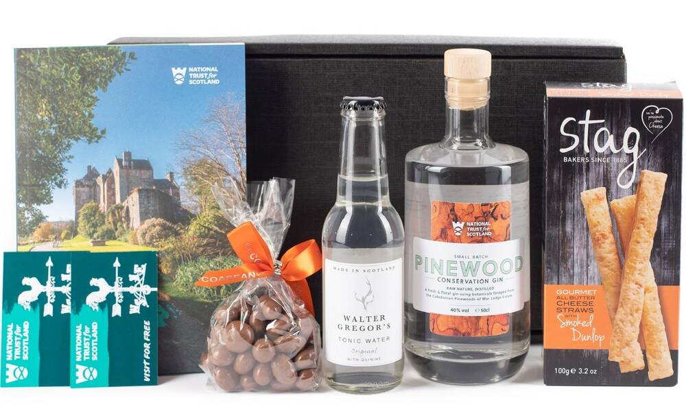 The contents of a gin hamper are displayed in front of the black card box. From the left are two tickets for Trust places, a copy of the National Trust for Scotland guide, a bag of chocolates, a bottle of tonic water, a bottle of gin and a box of cheese straws.