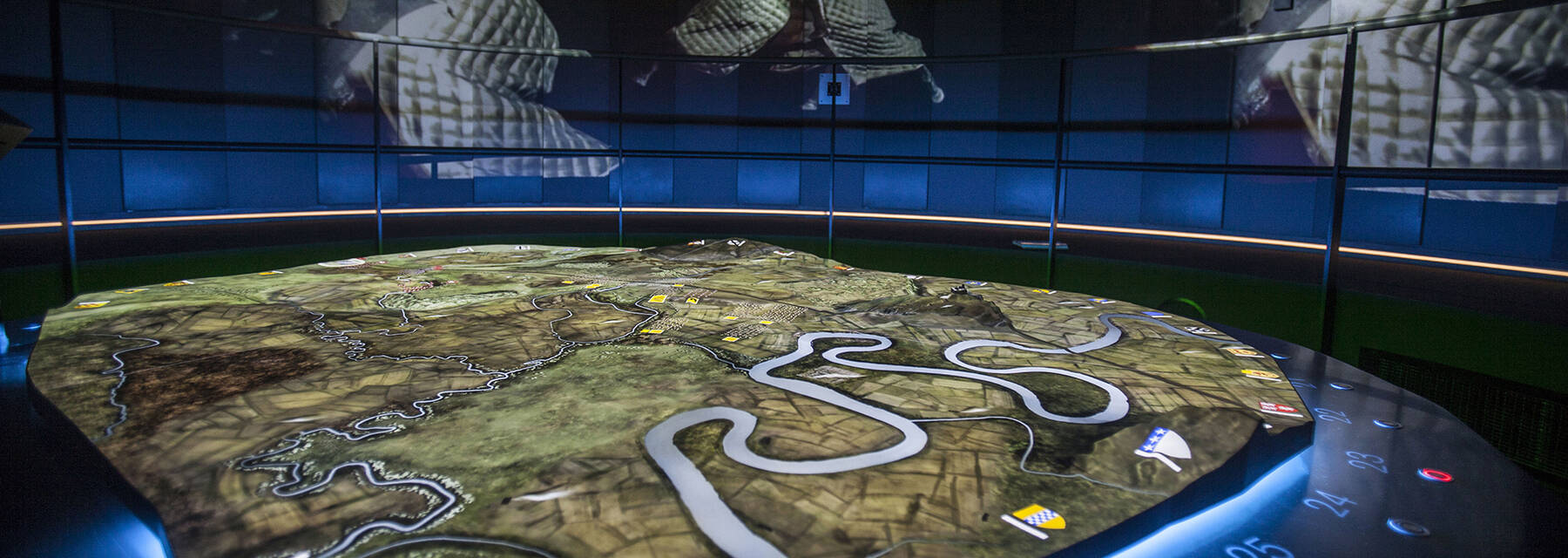 A view of the lit, digital battle table at the Battle of Bannockburn experience. The table shows a map of the battle area, with various heraldic flags around the outside. The walls of the dark room are covered with panels that have images of knights on horses.