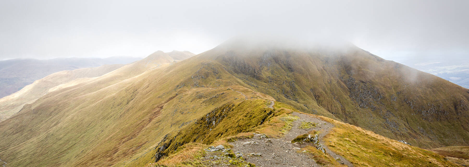 Mist blanketing the peak of Ben Lawers, with a ridge path running into the foreground.