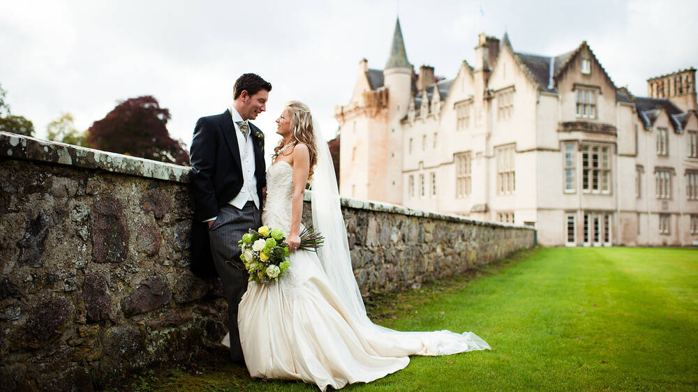 Wedding couple standing in front of Brodie Castle.
