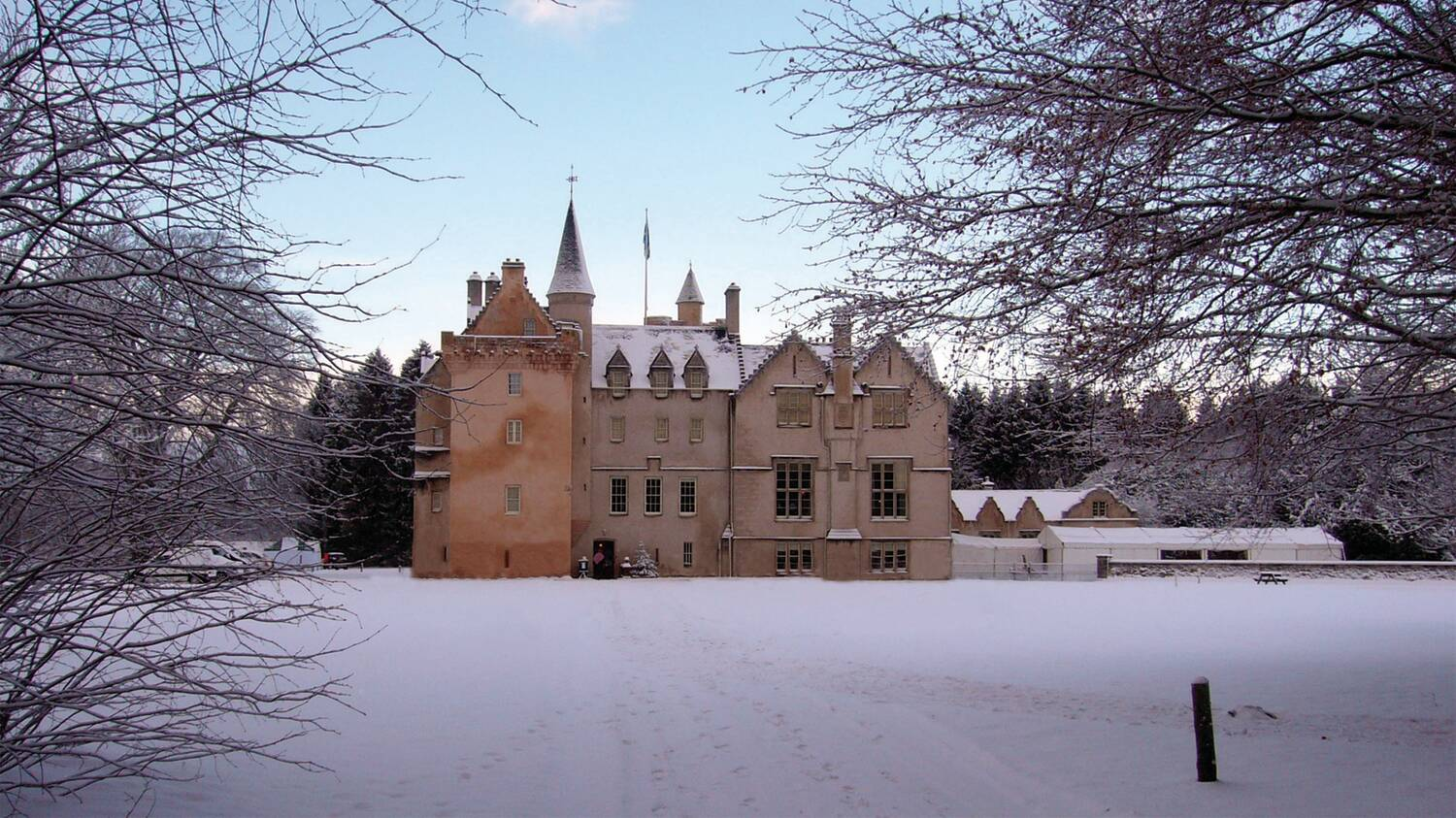 A view of Brodie Castle after heavy snowfall. The lawns and trees are blanketed with snow. The sky is a pale blue. The walls of the castle look even more orange in contrast.