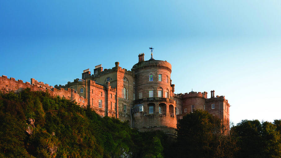 A view of Culzean Castle at dusk, with the setting sun making the walls glow red. The castle is seen from the beach below.
