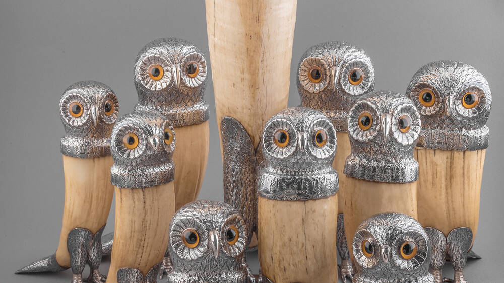 A group of 19th-century owl-shaped drinking horns, with 9 small owls and 1 very tall one.The bases are made from a light-brown horn, and all have a silver owl head on top, with orange eyes.