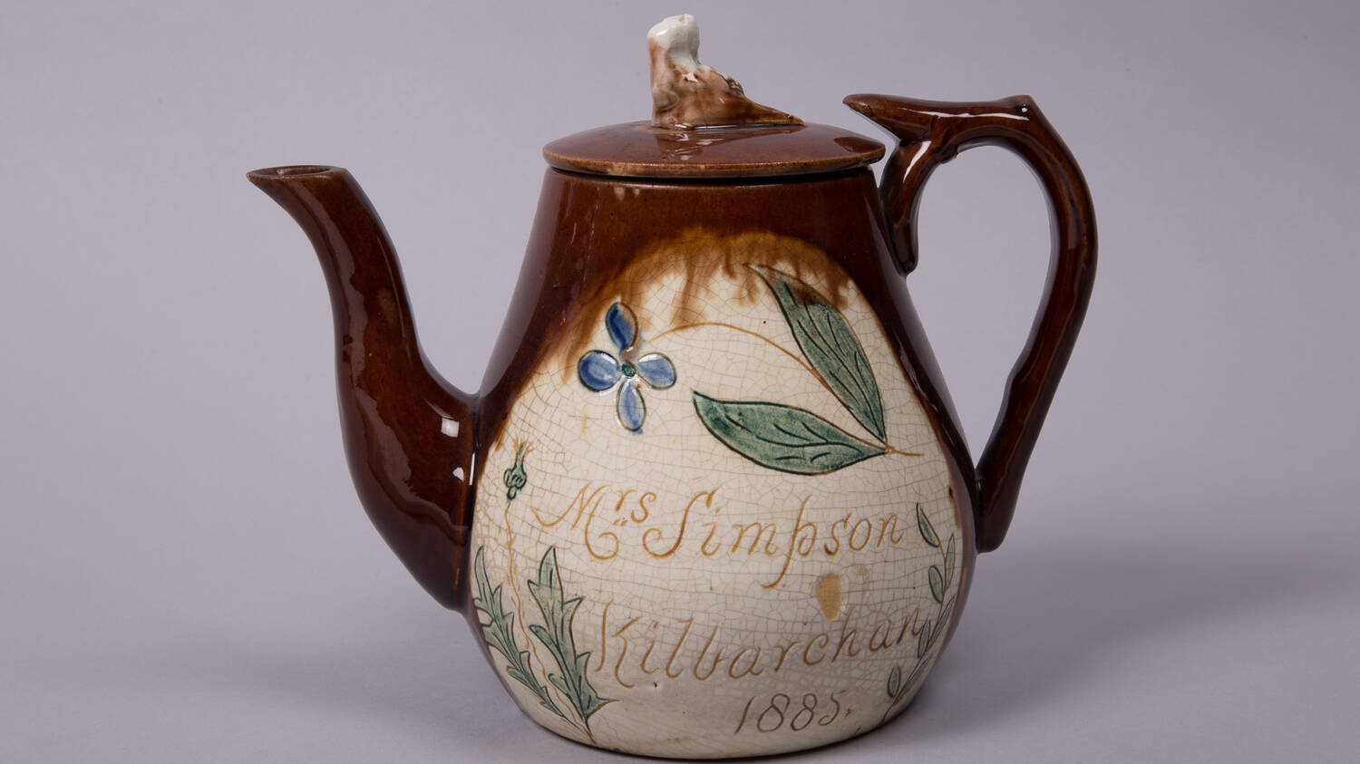A varnished ceramic teapot with a brown spout and handle. The body has leaves and flowers painted on it, as well as the words: Mrs Simpson, Kilbarchan 1885.