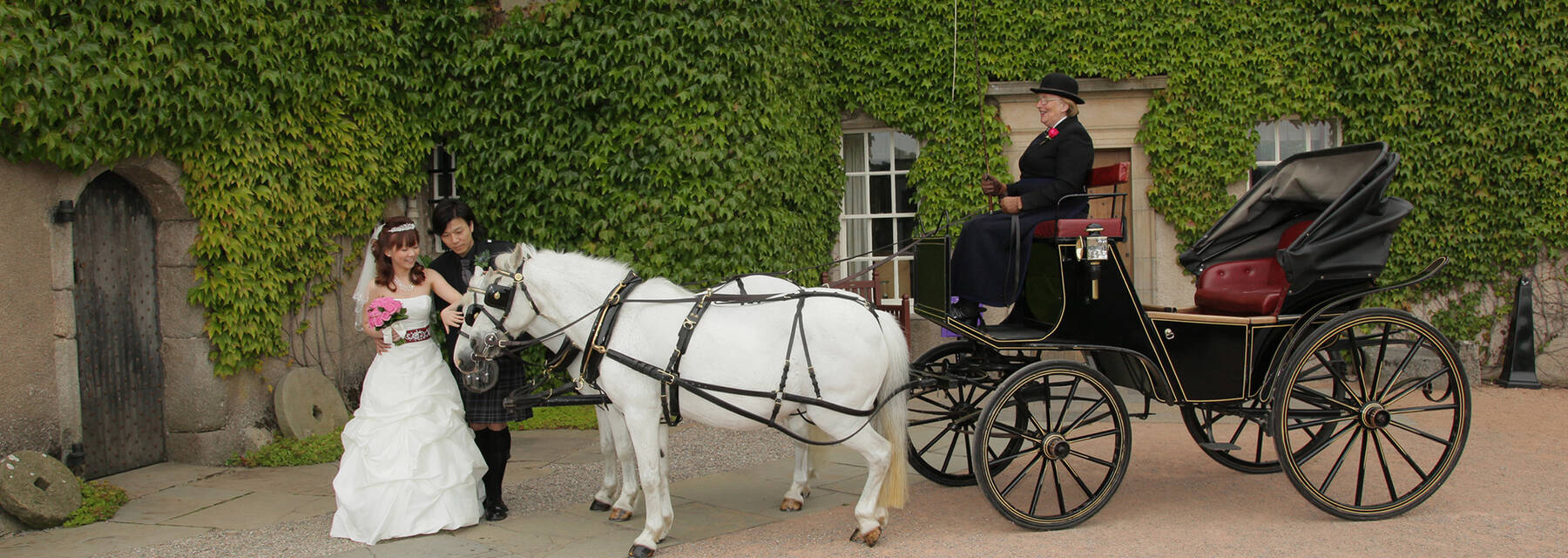 Wedding couple with pony and trap outside Crathes Castle